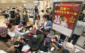 福岡市の百貨店で始まったソフトバンクホークスの優勝記念セールで商品を手に取る買い物客=4日午前