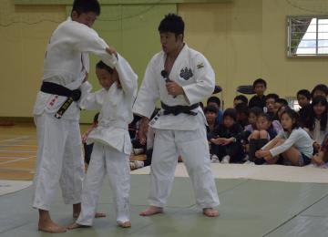 柔道の五輪銀メダリスト、平岡拓晃さん(右)が児童に投げ方を指導した=下妻市高道祖