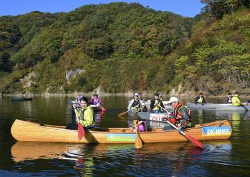 秋田市に避難していた福島県民らが製作したカヌー(手前)に乗る吉田美和さんと長女美都ちゃん。右は中村昭三さん=4日、福島県楢葉町