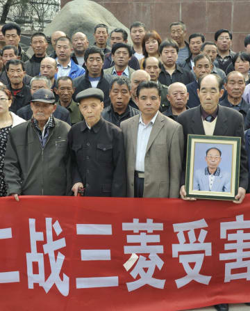 第2次大戦中の中国人強制連行を巡る損害賠償などの訴状提出前、公園に集まった生存者(前列左端と2人目)と遺族ら=2014年4月、中国河北省石家荘市(共同)