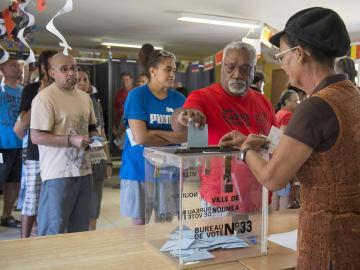 4日、フランス特別自治体ニューカレドニアの政庁所在地ヌメアにある投票所で一票を投じる男性ら(AP=共同)
