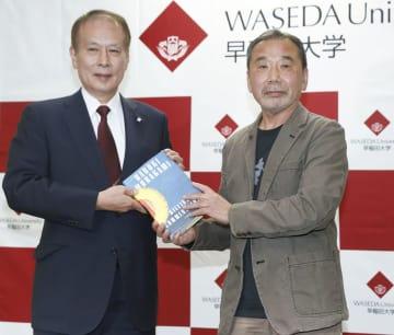 早大の鎌田薫総長(左)に寄贈する書籍を手渡す作家の村上春樹さん=4日午後、東京都新宿区