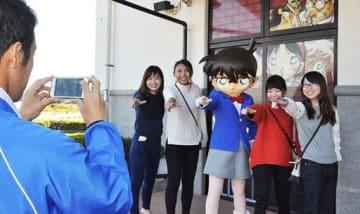 コナン君と一緒に写真を撮る来館者ら=4日、北栄町由良宿の青山剛昌ふるさと館