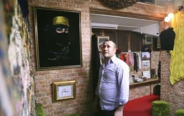 自ら経営するカフェの壁に飾ったアラブの絵画を眺め、故郷に思いをはせるユセフ・ジュディさん=2018年10月2日、さいたま市