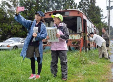 自撮りでチェック地点の廃バスを撮影する参加者ら