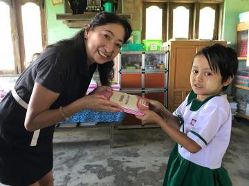 ミャンマーの小学生(右)にノートを手渡す益子しげ美さん(益子さん提供)