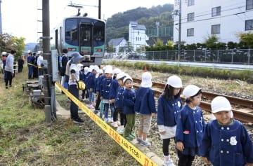 大津波を想定した避難訓練で、緊急停止した列車から高台へ避難する子どもたち=5日午前、福井県高浜町