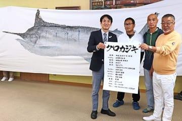 【田嶋勝正町長(左)にクロカジキの魚拓を寄贈したチーム「天晴」のメンバー=和歌山県串本町串本で】