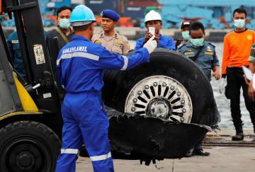 5日、インドネシアの首都ジャカルタのタンジュンプリオク港で、損傷した事故機のタイヤを運ぶ作業員ら(ロイター=共同)