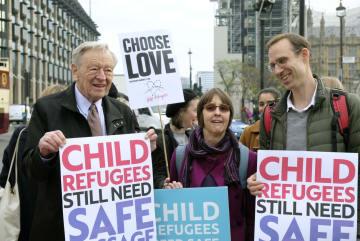 5日、ロンドンの英議会前でプラカードを手にするアルフ・ダブス上院議員(左)ら(共同)