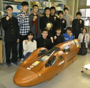 「Hondaエコマイレッジチャレンジ」の全国大会を制した自動車工学部の部員たちと「NP号●」