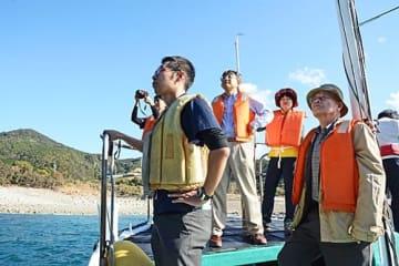【ガイドの案内で船上から褶曲を眺める日本ジオパーク委員会委員ら(6日、和歌山県すさみ町口和深で)】