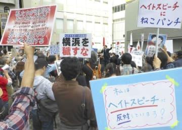 移民政策反対を掲げる団体主催の集会に、プラカードを掲げ抗議する市民ら=10月14日、横浜市鶴見区