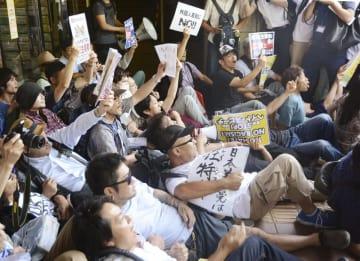 川崎市の市教育文化会館で開催予定だった集会に抗議し、座り込む市民ら
