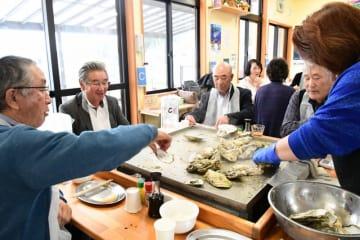 カキ小屋で蒸しカキの食べ放題を堪能する観光客