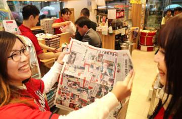 黒田さんから新井選手への全面広告が掲載された新聞を手に喜ぶカープファン