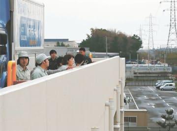 津波避難ビルに駆け上がり、周囲の様子を見渡す訓練参加者=5日午前9時ごろ、仙台市宮城野区港2丁目のセンコー