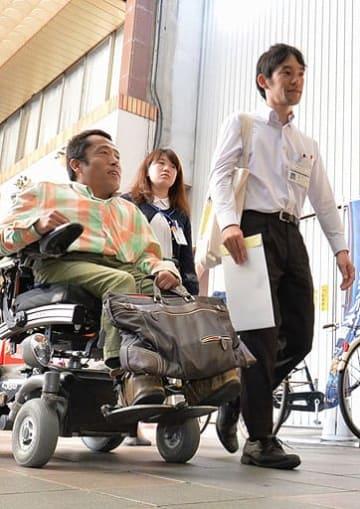 六條さん(左)と茨木市障害福祉課の職員が一緒に茨木阪急本通商店街を歩き、街にある社会的障壁を探る=10月、茨木市元町