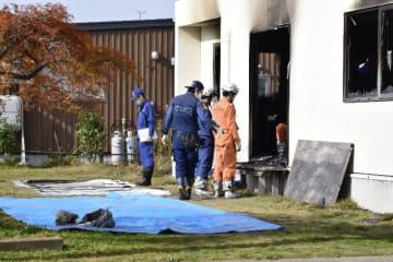 少年が放火した疑いが持たれている住宅を調べる捜査員ら=6日午前10時ごろ、十和田市