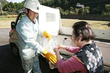 【ごみを受け取る町清掃センター職員(左)=6日、和歌山県白浜町椿で】