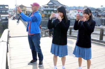 錦帯橋上でSNSに投稿する写真を撮影するみなみさん(右)、千穂さん(中)、ウォルシュさん