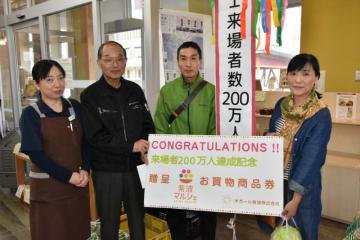 200万人目となった(右から)勝山朋子さんと裕之さん夫妻に商品券を贈る(左から)石上直美店長と佐々木広社長