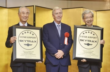 5スターを証明する盾を手にする羽田空港のターミナルビル運営会社幹部ら=7日午後、羽田空港