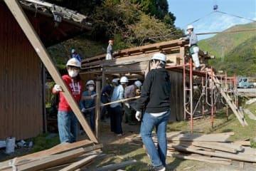 納屋を解体して古材を仕分けるイベント参加者=五木村