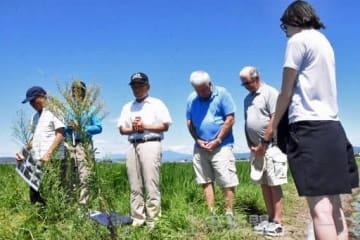 邑楽町秋妻のB29墜落地点で米国の関係者と一緒に黙とうする新井さん(中央)=8月