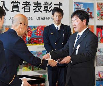 城戸局長から表彰状を受け取る渡辺さん(右)
