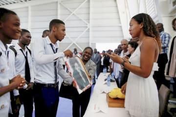 7日、ハイチの首都ポルトープランス近郊のスポーツセンターを訪れ、地元の人から絵を受け取る大坂なおみ(ロイター=共同)