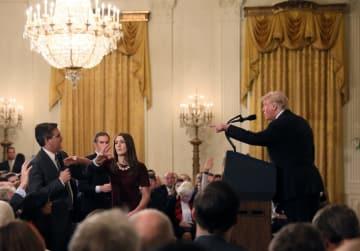 米ホワイトハウスでのトランプ大統領の記者会見で、質問するCNNテレビ記者(左端)のマイクに手を伸ばす当局者=7日(ロイター=共同)