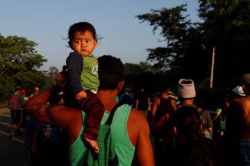 7日、メキシコ南部で9カ月の娘を背負い、米国に向かって歩くホンジュラス出身の移民(ロイター=共同)