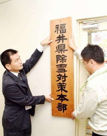 県除雪対策本部の看板を掲げる大槻土木部長(左)ら=11月7日、福井県庁