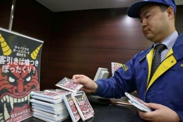 客引きへの注意を促すティッシュやチラシをホテルのフロントに置く熊本中央署員=7日、熊本市中央区