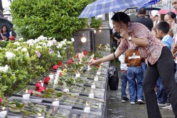 8日、フィリピン・パロの大聖堂で墓に花を手向ける女性(共同)