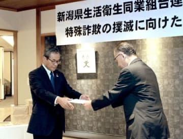 県警の栗原良光生活安全部長(右)から要請書を受け取る野沢幸司会長=8日、田上町
