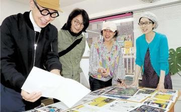 20周年タイムマシン号の誌面を確認する菊地さん(左端)、木村さん(左から3人目)ら=仙台市青葉区