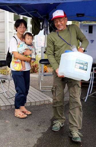 親子連れの住民のために水を運ぶ給水ボランティアの谷井さん(右)