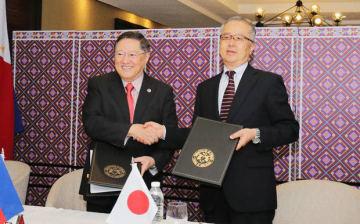 MRT3号線改修事業への円借款契約を交わしたJICAの田中氏(右)とフィリピンのドミンゲス財務相=8日、首都圏マニラ市(NNA撮影)