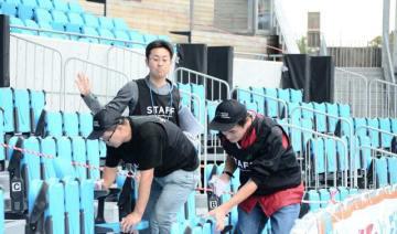 スタンドの座席を丁寧に拭く就労体験の参加者ら=川崎市中原区の等々力陸上競技場
