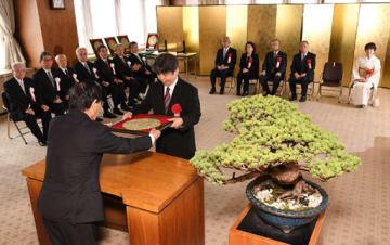 岡谷社長(手前)から賞牌を受け取る細川さん。正面後方は左から江幡さん、小林さんの代理の妻恵美子さん、角広さん、馬場さん、山脇さんの代理の妻由起子さん