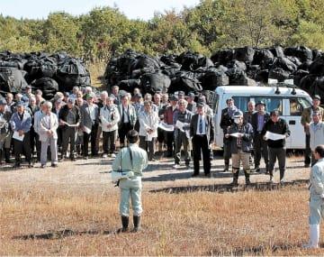 加美町が汚染牧草を集約管理する旧宮崎田代放牧場。猪股町長(手前中央)が行政区長に、すき込みへの理解を求めた=10月18日