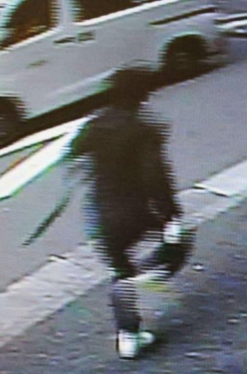 名古屋市の路上で現金約3800万円入りバッグが奪われた事件で、近くのビルの防犯カメラに写った走り去る不審者=8日