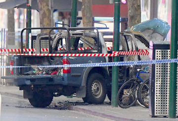 9日、オーストラリア南東部メルボルンの現場付近に残された炎上した車(ロイター=共同)