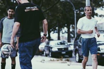 サッカーしている青年たちの横を走るフィンランドのチャンピオン - Illumine Films