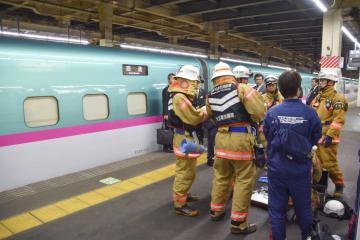 煙が確認された東北新幹線の車両脇に立つ消防隊員ら=9日午後7時28分、JR大宮駅