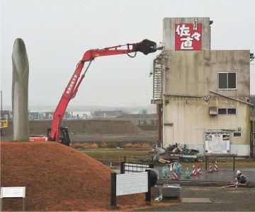 解体工事が始まった佐々直の旧本店工場。左は慰霊碑=9日午前9時40分、名取市閖上