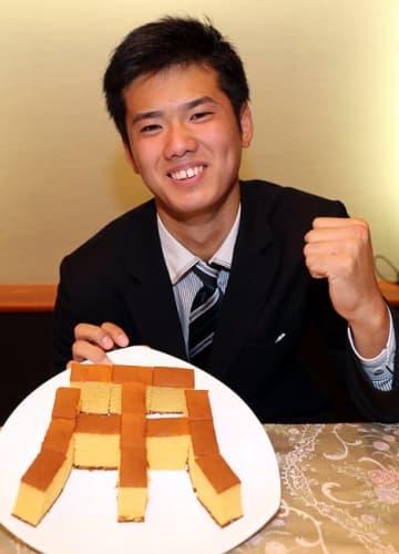 長崎名物カステラを阪神のロゴに見立てポーズをとる創成館高の川原=ホテルニュー長崎