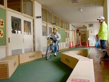 旧校舎を自転車に乗って疾走する参加者=美濃市下河和、洲原生涯学習センター